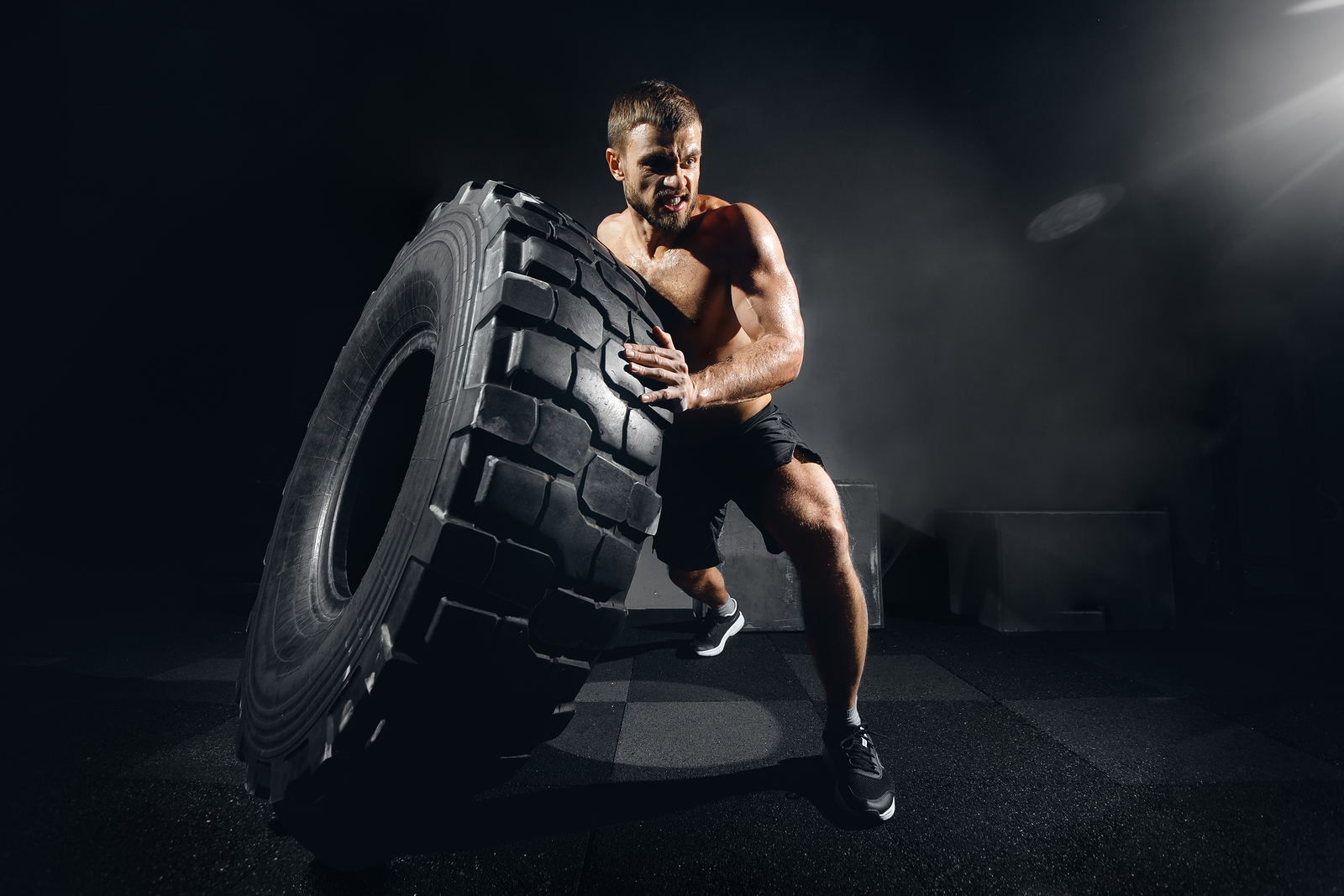 Muscular Fitness Shirtless Man Moving Large Tire In Gym Fitness
